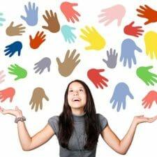 viele bunte Hände fliegen um eine Frau